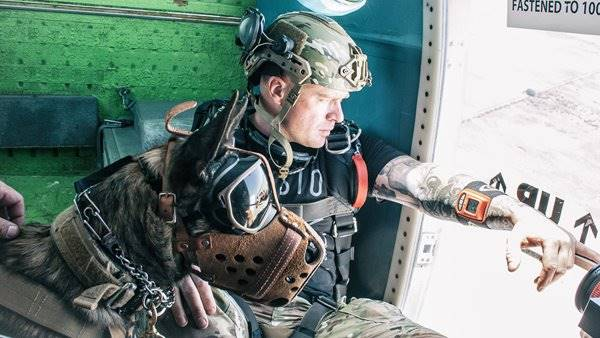 Robbie Hill of Mission Volant wearing his MultiCam EXFIL Ballistic helmet in a helicopter before he jumps with a working dog.